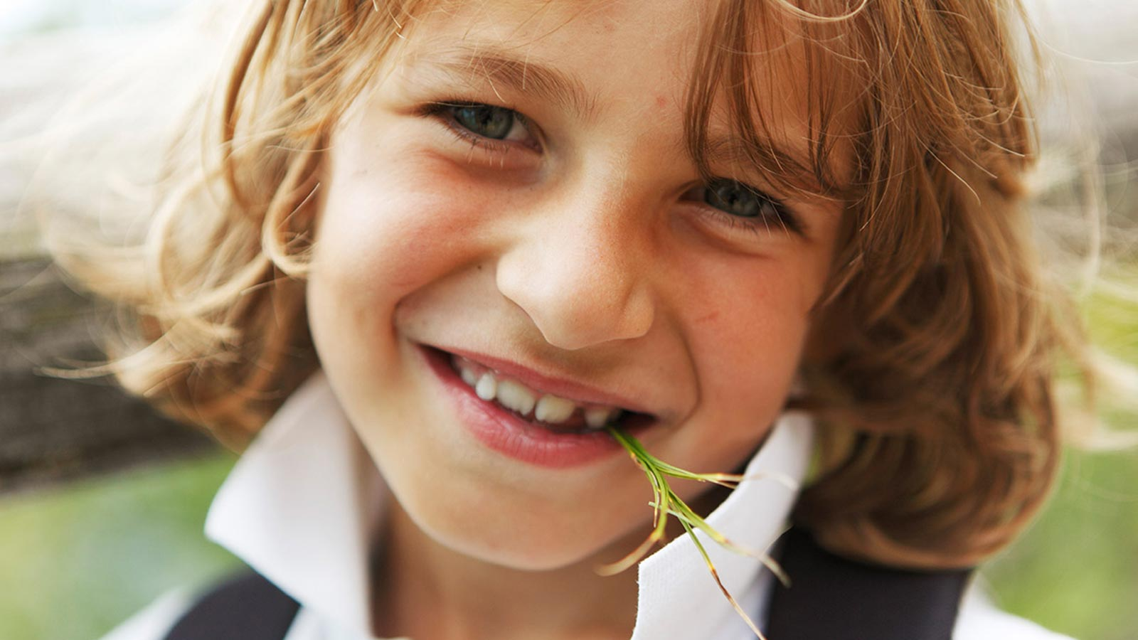 A child smiles with a sprig of rosemary in his mouth during a family holiday in South Tyrol