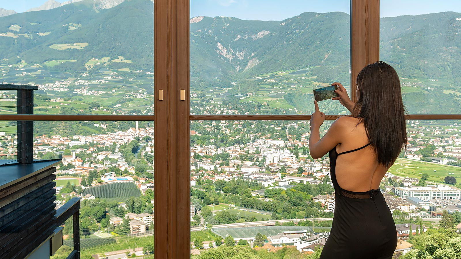 A girl photographs the city of Merano from the hall in our residence in Marlengo