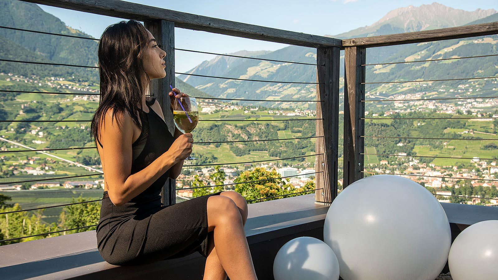 A girl drinks an aperitif on the terrace of the Residence Aqualis in Marlengo near Merano