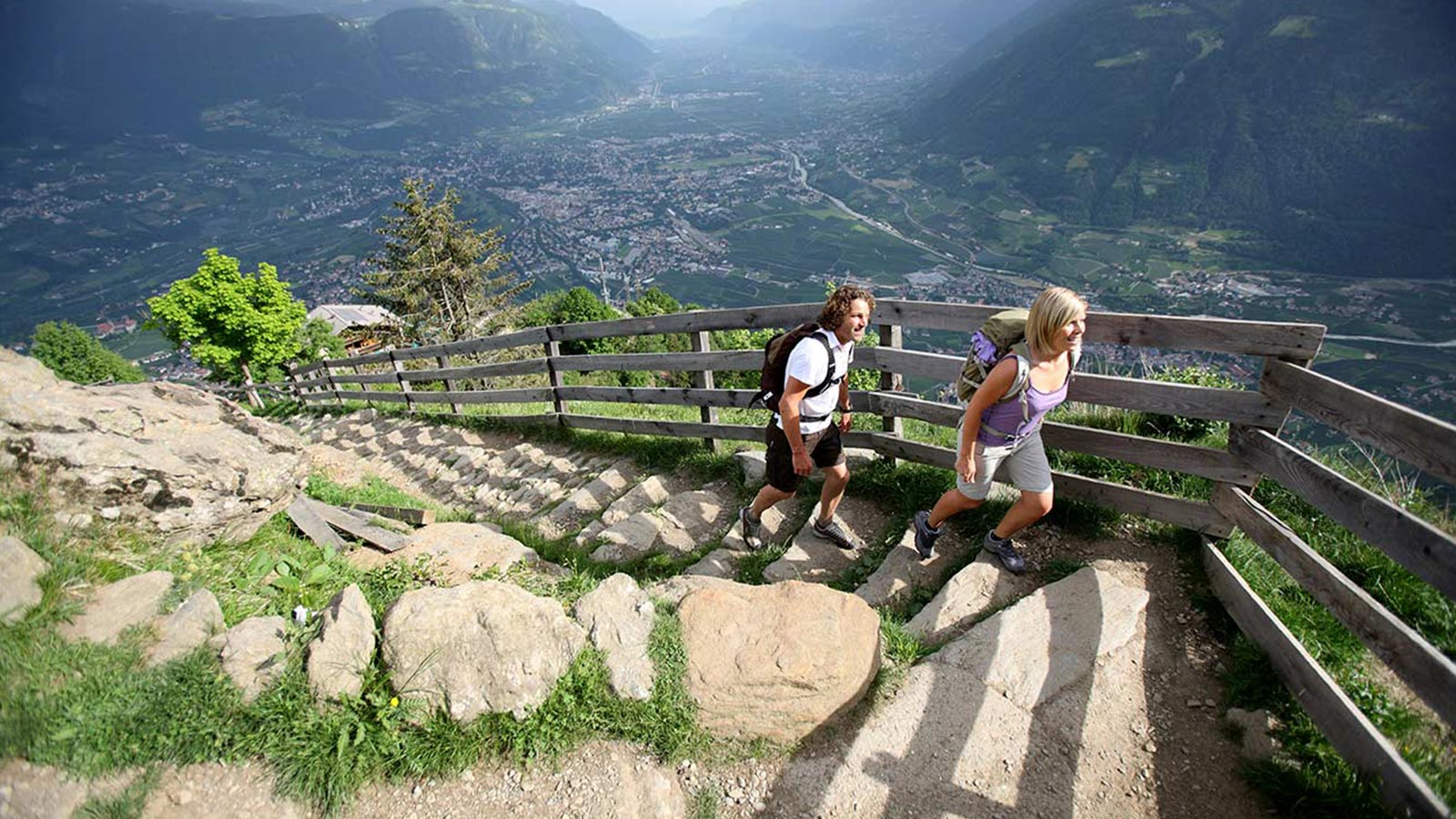 A couple hiking on a path with a view of the city of Merano