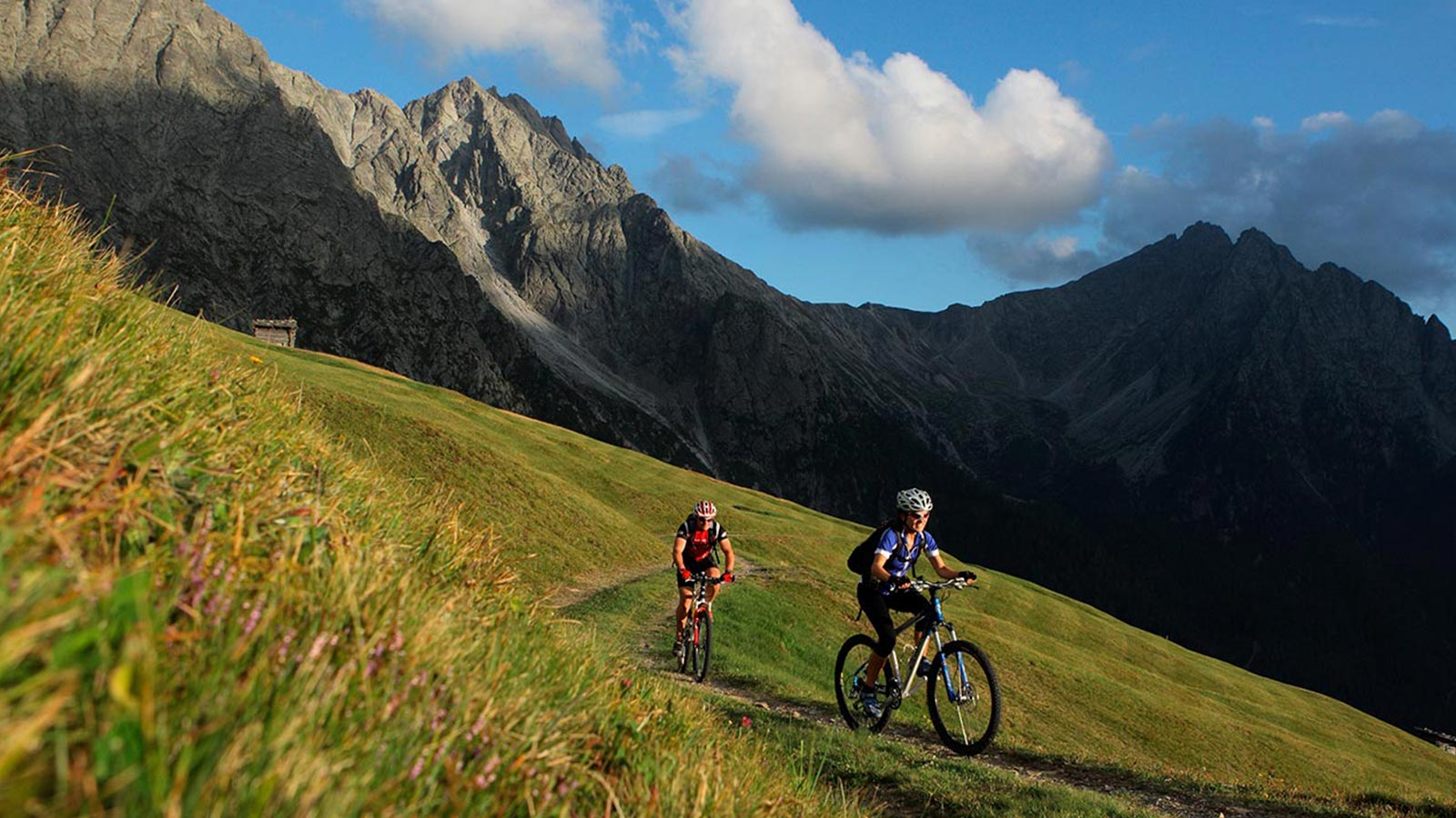 A couple enjoy mountain biking during a sunny day in the Dolomites