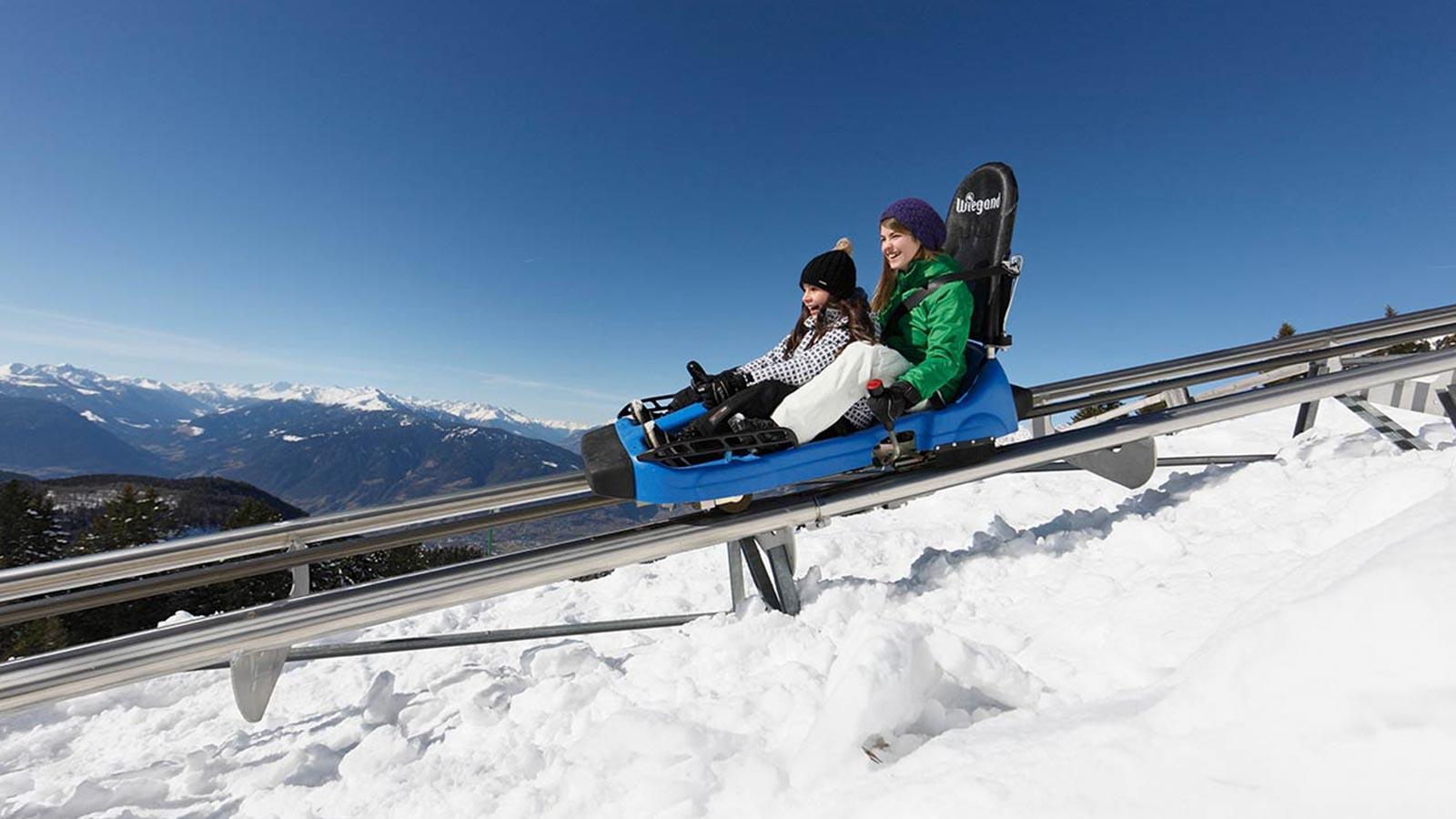 Two girls on the Alpin Bob sledge on rails