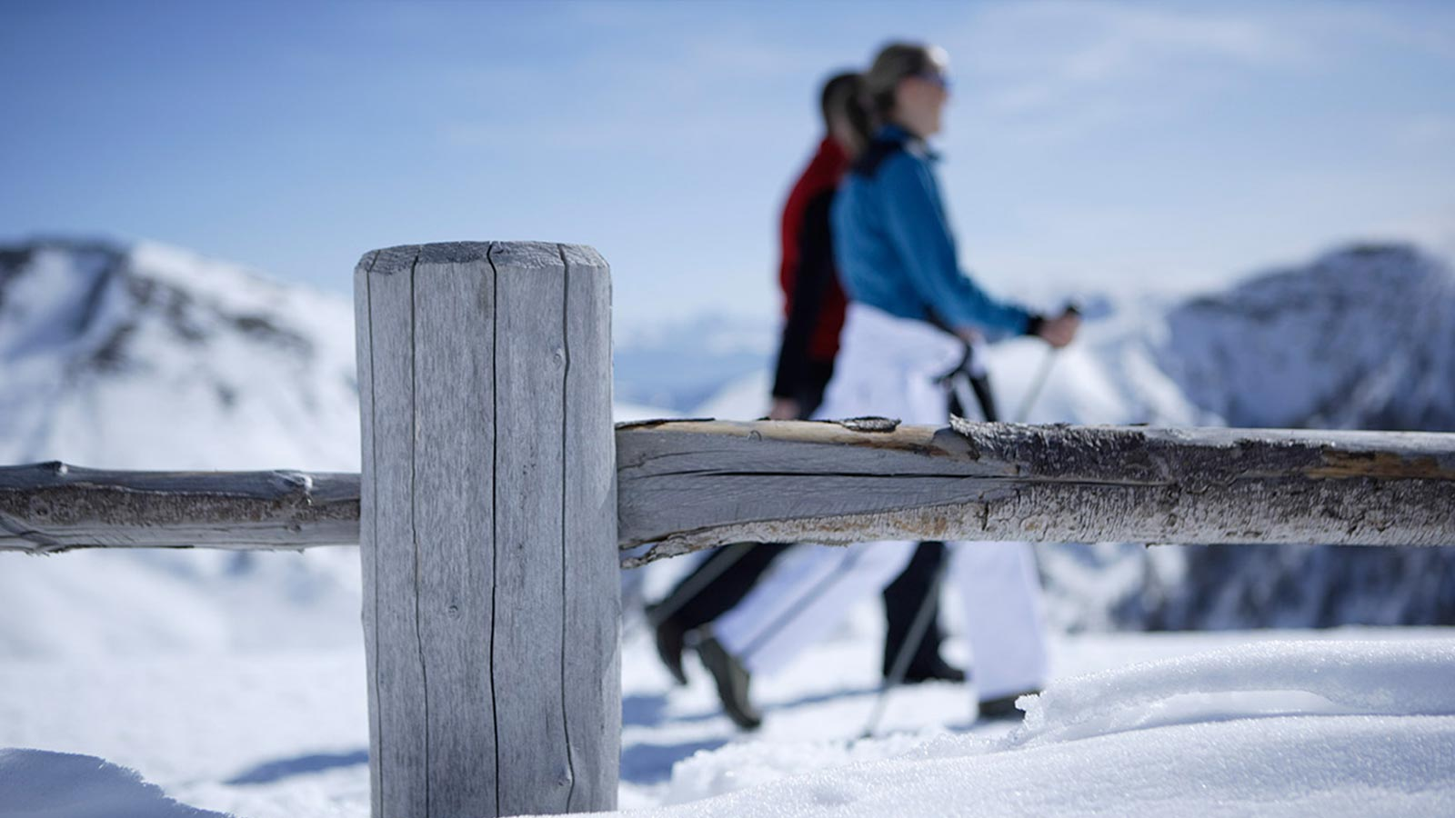 Detail of a fence with a couple walking in the snow in the background